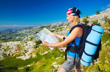 expedition: Cute blond girl in the mountains looking way on the map, summer vacation, active lifestyle, tourism and expedition concept Stock Photo