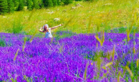 Beautiful blond woman sitting down on lavender field with raised up hands, enjoying sunny day, spring nature photo
