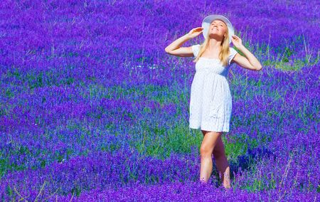 Cute blond teen girl standing on purple lavender meadow, woman wearing white dress and hat take sun bath on floral field Stock Photo