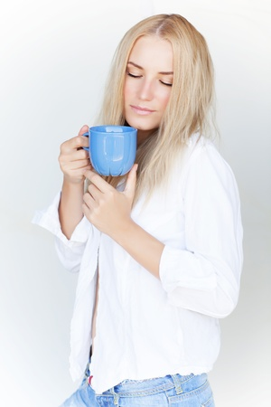 Attractive blond female with closed eyes enjoying tasty tea isolated ob white background, pleasure concept  photo