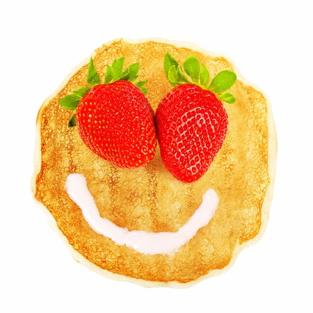 breakfast smiley face: Tasty fried pancake with beautiful smiley face isolated on white background, red strawberry eyes, white creamy mouth, sweet dessert Stock Photo