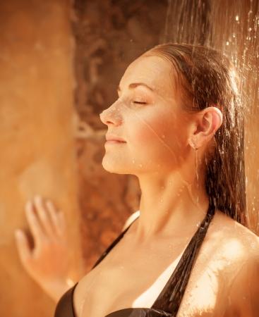 mujer bañandose: Primer plano de una hermosa mujer toma la ducha al aire libre, linda chica con los ojos cerrados, disfrutando del agua fría y fresca, cuidado del cuerpo y el concepto de la higiene