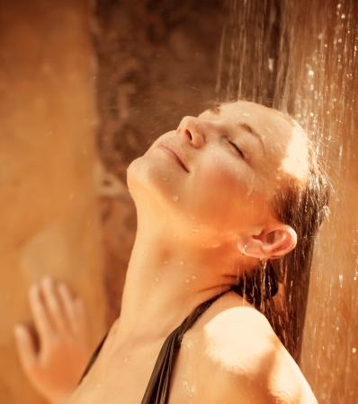 mujer bañandose: Retrato de detalle de Linda niña con los ojos cerrados que toma la ducha al aire libre después de la playa, el concepto de placer