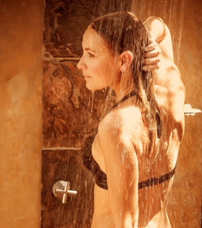 Beautiful young lady taking shower outdoor, bright sun light, luxury spa salon, wellness and hygiene concept  photo