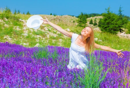 Pretty girl sitting down on purple lavender field, enjoying warm sun light, holding in hand white summer hat, summertime nature, holiday and vacation concept photo