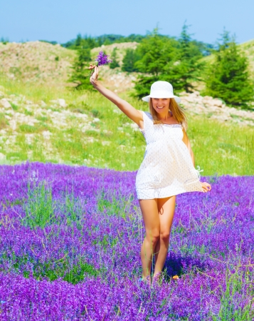 Cute girl wearing white hat holding in hand beautiful purple lavender flowers, dancing on floral glade, summer time season photo