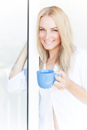 Closeup portrait of beautiful blond woman drinking tea at home near window, morning beverage, peace and happiness concept  photo