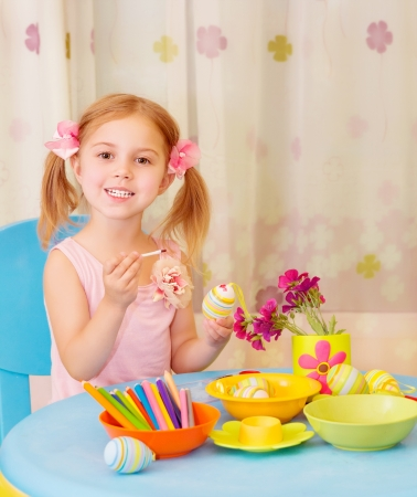 Sweet little girl paint Easter eggs on drawing lesson, having fun in daycare, traditional Christian holiday, joy and pleasure concept photo