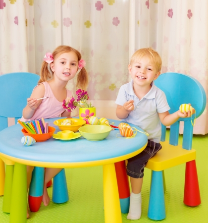creative egg painting: Two cheerful kids paint Easter eggs at home, handmade festive decorations, spring holiday, happiness concept