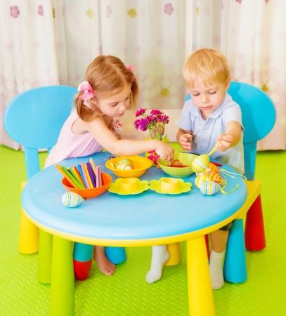 preescolar: Felices los ni�os lindos hacen los huevos pintados en la escuela, s�mbolo tradicional de Pascua, lecci�n de arte, los mejores amigos de dibujo en el aula