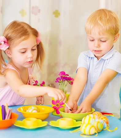 creative egg painting: Two serious children paint Easter eggs at home, using colorful decoration, Christian holiday concept