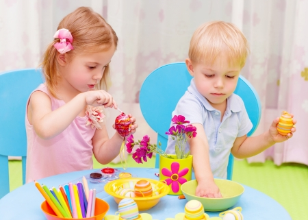 Two adorable children paint Easter eggs in kindergarten, drawing lessons, colorful decorations, traditional Eastertime art photo