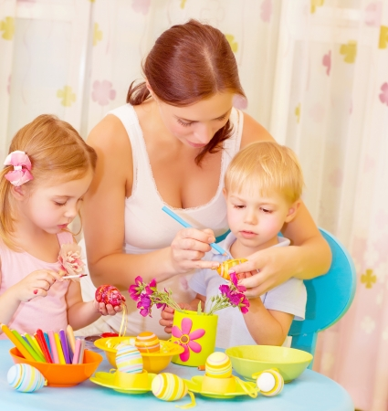 Two small cute children with beautiful mother paint Easter eggs at home, mom teaching babies decorate traditional eastertime symbol photo