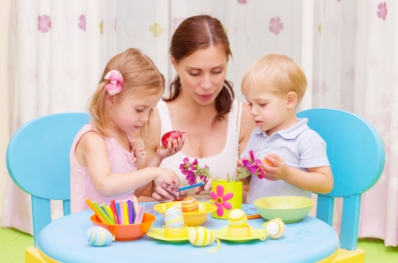Beautiful young mother with two sweet kids decorated traditional Easter eggs with colorful paint, happy family concept Stock Photo - 19335045
