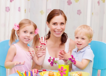 Happy young family playing with colorful paint at home, mother with two adorable children decorate Easter eggs photo
