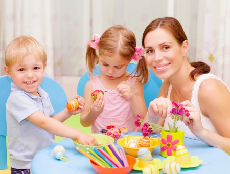 daycare: Two sweet toddler with young drawing teacher paint colorful Easter eggs, art lesson, handmade festive decor Stock Photo