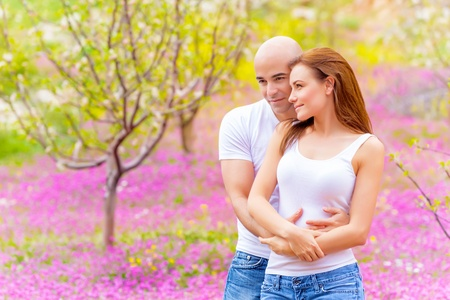 Lovers hugging outdoors in springtime, spending time on backyard, pink floral meadow, enjoying family, love concept photo