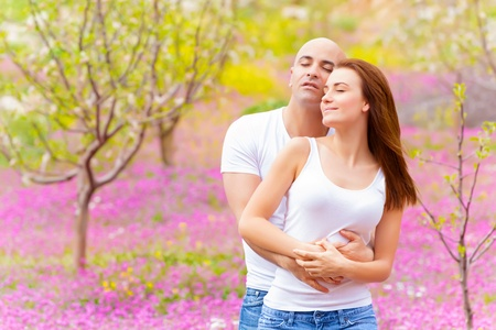 Happy loving family hugging in spring park on beautiful pink floral meadow, enjoying each other with closed eyes, springtime weekend, love concept  photo