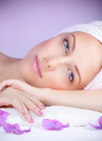Gros plan portrait d'une femme belle au salon spa fixant sur la table de massage, profitant dayspa, fond pourpre, soins de beauté