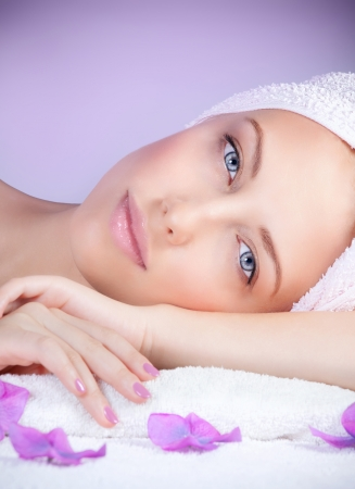 tratamientos corporales: Retrato de mujer hermosa en sal�n del balneario que se establecen en la mesa de masaje, disfrutando dayspa, fondo p�rpura, tratamientos de belleza