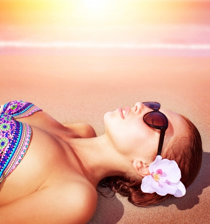 Closeup of beautiful female lying down on sea shore on sunset background, relaxed on the beach, luxury spa resort, summer holiday and vacation concept photo