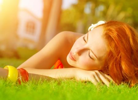 so�ando: Mujer pelirroja linda que se acuesta en la hierba fresca y verde con los ojos cerrados, al aire libre para dormir, disfrutando de spa, resort de lujo, la luz del sol caliente, vacaciones de verano y concepto de vacaciones Foto de archivo