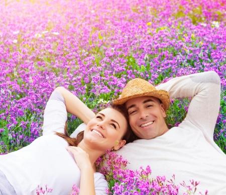 lavanda: Hermosa pareja feliz acostado en el campo de lavanda p�rpura, que se divierten en el claro floral, la naturaleza de verano, concepto del amor