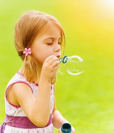 burbujas de jabon: Primer retrato de niña linda que sopla burbujas de jabón en el parque de la primavera, que se divierten al aire libre, concepto de infancia feliz