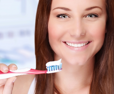 oral hygiene: Closeup portrait of beautiful young woman brushing her teeth in bathroom, perfect smile, dental care, healthy lifestyle concept Stock Photo