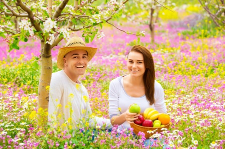 Happy smiling couple on picnic in beautiful blooming garden, eating tasty fresh fruits, enjoying spring nature photo