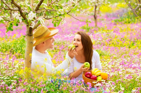 Two lovers on picnic in beautiful spring garden, purple flowers field, blooming tree, handsome man feeding girlfriend green apple photo