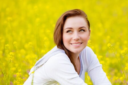 adult rape: Closeup portrait of beautiful young female sitting down on fresh yellow floral field, coleseed meadow, summer vacation, relaxation outdoors