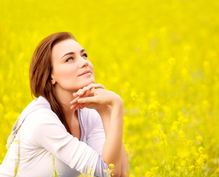 rape: Closeup portrait of attractive brunette female sitting down on yellow floral field, rapeseed plantation, summer vacation concept Stock Photo