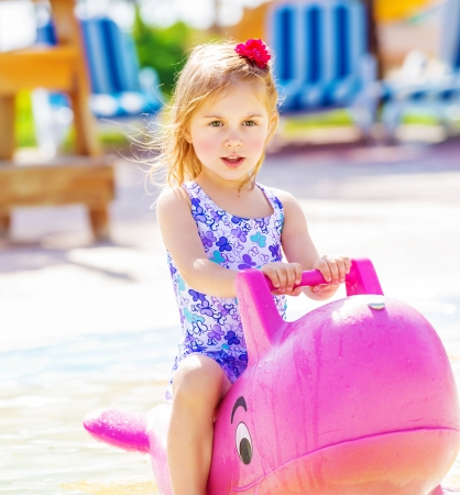 Closeup of active baby girl swimming in the pool on big pink inflatable dolphin, water attractions in childs camp, summer holidays concept  Stock Photo