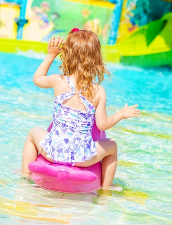 Rear view of sweet little girl wearing beautiful swimwear having fun on water attractions in aquapark, happy childhood, summer holiday concept