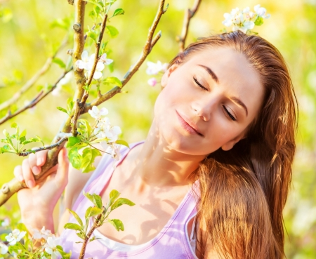 Closeup photo of cute girl with closed eyes outdoors, sunny day, blooming tree, spring garden, carefree concept