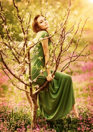 Fairy-tail forest nymph, beautiful sexy woman at spring garden, wearing long dress, sitting on blooming tree, vintage dreamy fashion style photo