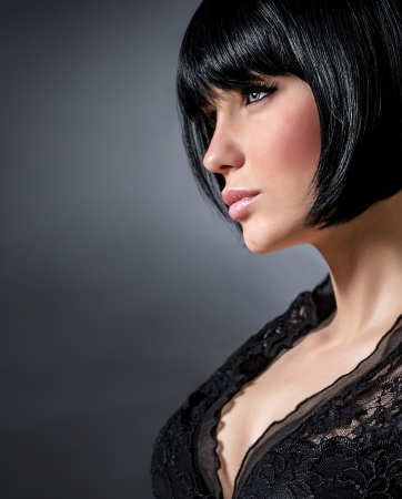 Closeup portrait of sexy woman with stylish short haircut isolated on dark background, profile of seductive brunette female with perfect makeup, beauty salon photo