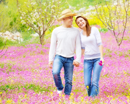 Young loving couple walk in spring park, first love, romantic date, springtime holidays, spending time together outdoors photo