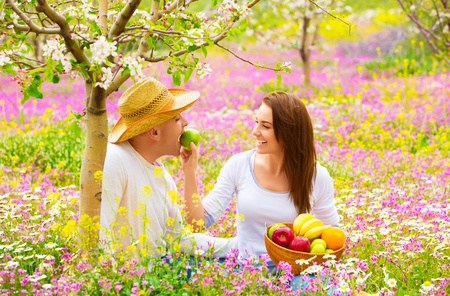 Young happy family having fun in spring blooming garden, cute woman feeding her boyfriend apple, romance and love concept photo