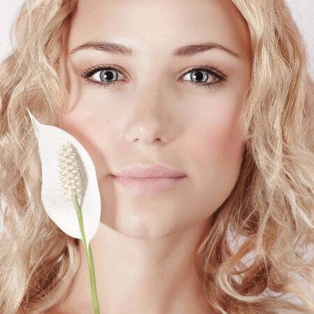 calla lily: Closeup portrait of cute girl with blond curly hair holding gentle white calla flower, enjoying day spa, beauty salon concept Stock Photo
