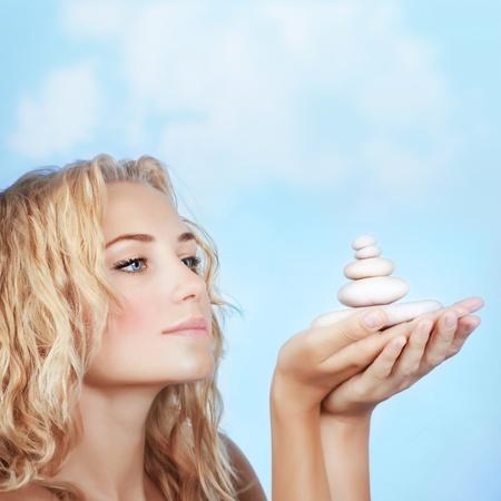 piedras zen: Retrato de muchacha bonita rubia con piedras del balneario al aire libre, tratamientos de belleza, salón de spa de lujo, aire libre relajación, el equilibrio zen Foto de archivo