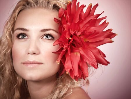 Closeup portrait of cute blond girl with big red flower in head isolated on pink background, natural makeup, spa concept Stock Photo - 19558212