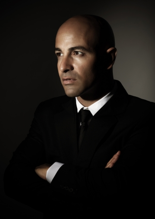 Portrait of handsome serious man wearing black stylish suit isolated on dark background, successful businessman photo