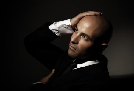 dresscode: Attractive bald arabian man wearing formal black suit, festive dresscode, mens fashion, executive manager Stock Photo
