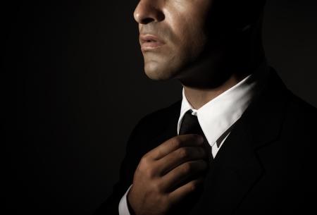 fixed: Hombre hermoso lazo fija joven aislado en el fondo negro, parte de la cara, exitoso hombre de negocios, moda para hombre, concepto de glamour Foto de archivo