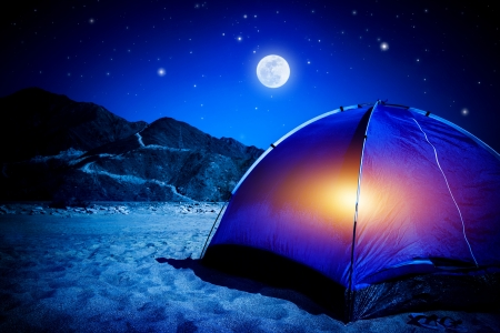 camping equipment: Camp on sandy beach, tent at the night with light inside, moon light, active tourism, hiking and traveling concept Stock Photo