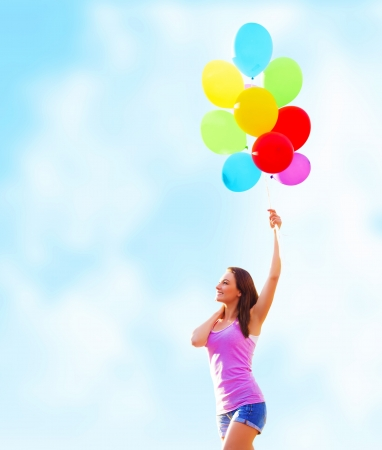Beautiful young woman holding in hand many colorful balloons on blue sky background, summer time holiday, fun concept  photo