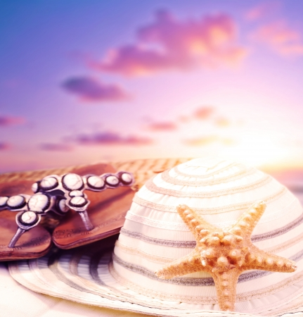 flops: Closeup still life of beach accessories on purple sunset background, flipflops and womens hat decorated with starfish, summer holiday and vacation concept  Stock Photo