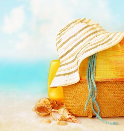 Accessori da spiaggia sulla sabbia vicino al mare, la protezione della pelle, conchiglia, cappello, borsa, day spa, resort tropicale, stile di vita lussuoso, vacanza estate